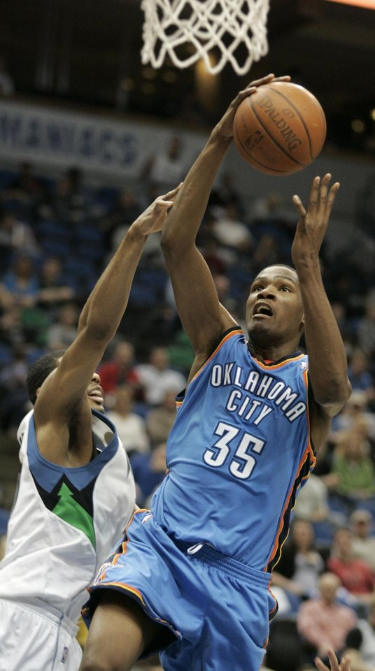Photo - Oklahoma City Thunder forward Kevin Durant (35) goes up for a shot against Minnesota Timberwolves forward Rodney Carney, left, during the first half in an NBA basketball game, Sunday, March 22, 2009 in Minneapolis. (AP Photo/Paul Battaglia) ORG XMIT: MNPB101