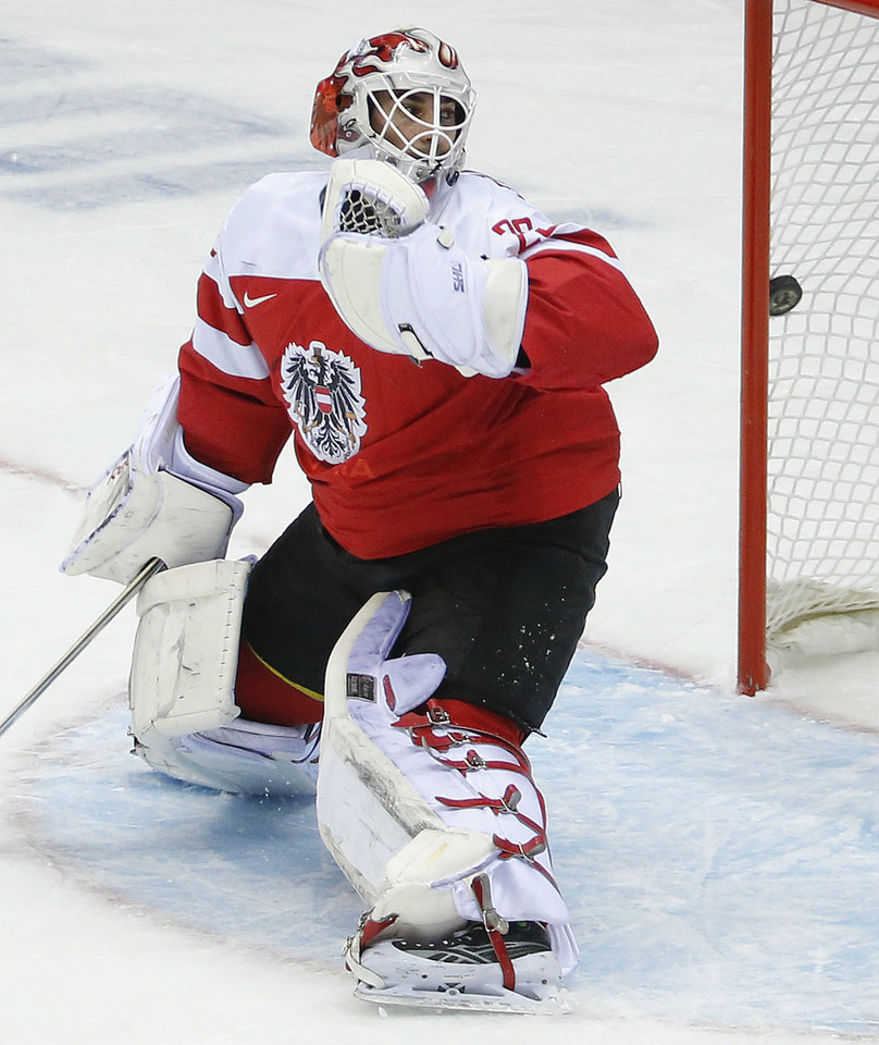 Photo - Austria goaltender Bernhard Starkbaum looks back as the puck hits the net for a goal by Finland in the first period of a men's ice hockey game at the 2014 Winter Olympics, Thursday, Feb. 13, 2014, in Sochi, Russia. (AP Photo/Mark Humphrey)