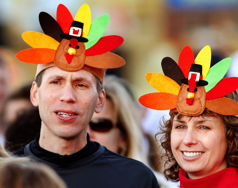 Photo - John and Amanda Daum  wear matching hats as they gather with other participants at the starting area for the one-mile wobble during the annual Turkey Trot in downtown Edmond Thursday morning,  Nov. 24, 2011.  Their daughter, Kylie, 7, also ran in the event.  Photo by Jim Beckel, The Oklahoman
