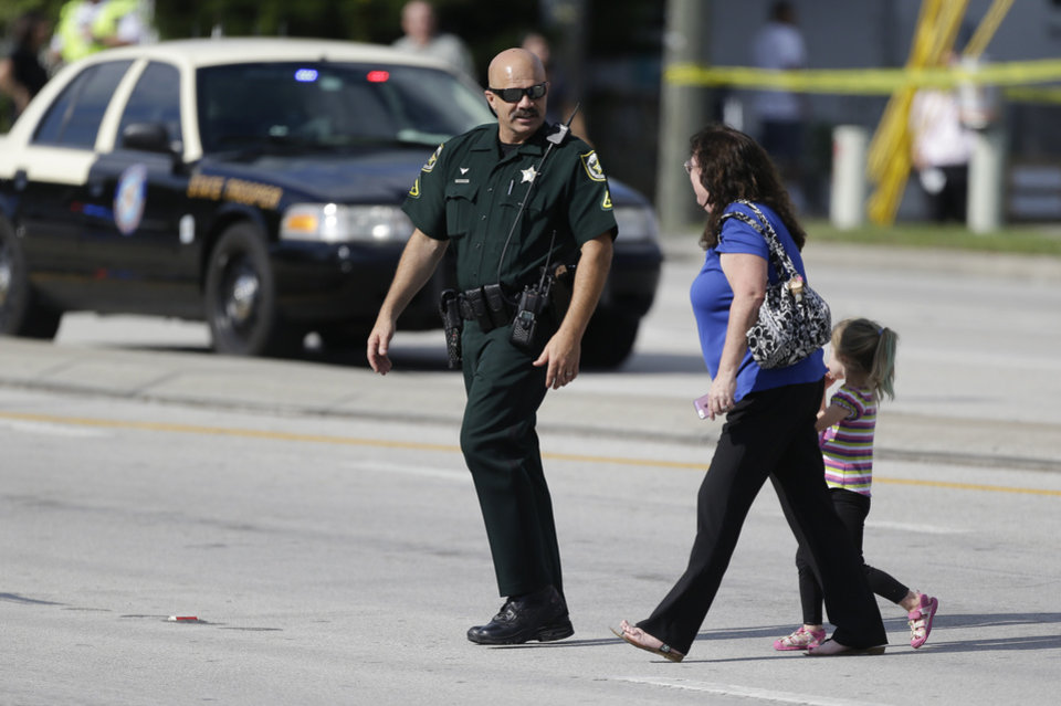 Photo - An Orange County Sheriff's deputy, left, escorts a mother and her child across a street after a vehicle crashed into a day care center, Wednesday, April 9, 2014, in Winter Park, Fla. At least 15 people were injured, including children. (AP Photo/John Raoux)