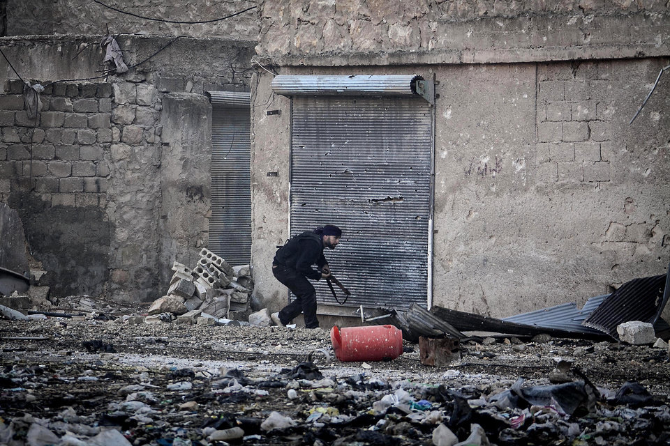 Photo - In this Wednesday, Dec. 5, 2012 photo, a Free Syrian Army fighter runs for cover during heavy clashes with government forces, not pictured, in Aleppo, Syria. (AP Photo/Narciso Contreras)