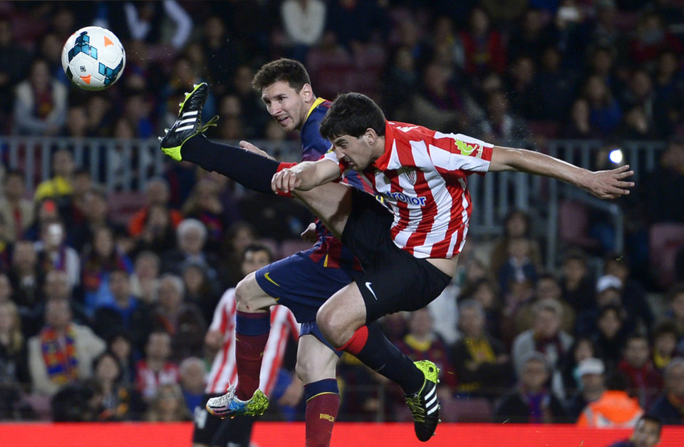 Photo - FC Barcelona's Lionel Messi, from Argentina, left, duels for the ball against Athletic Bilbao's Mikel San Jose during a Spanish La Liga soccer match at the Camp Nou stadium in Barcelona, Spain, Sunday April 20, 2014. (AP Photo/Manu Fernandez)