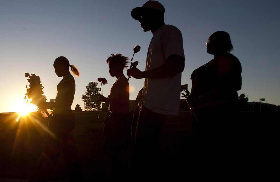 Photo -   From left, Tylecia Amos, 14, Shatyra Amos, 15, Michael Walker, 17, and Mykia Walker, 16, carry flowers to lay at a makeshift memorial across the street from the Century Theater parking lot, on Saturday, July 21, 2012 in Aurora, Colo. Twelve people were killed and dozens were injured in the attack early Friday at the packed theater during a showing of the Batman movie,