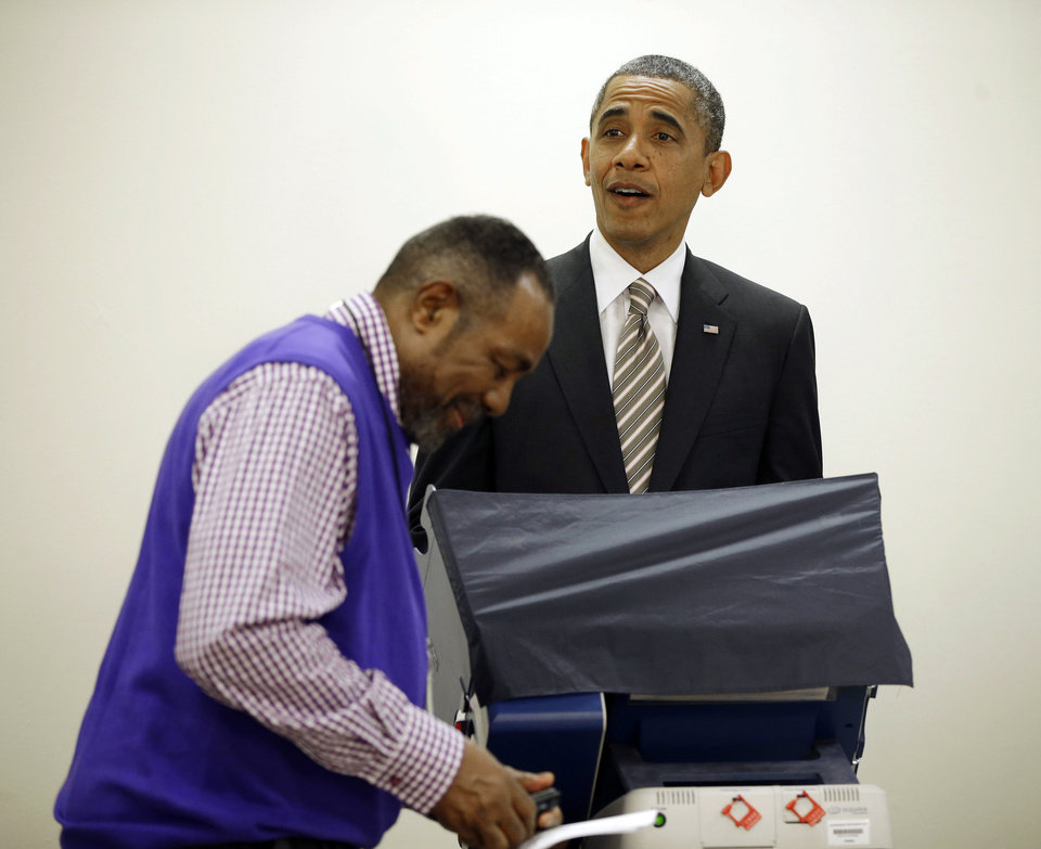Photo -   President Barack Obama, right, reacts to election official Eli Selph's cell ringing as he casts his vote, during early voting, in the 2012 election at the Martin Luther King Community Center, Thursday, Oct. 25, 2012, in Chicago. (AP Photo/Pablo Martinez Monsivais)
