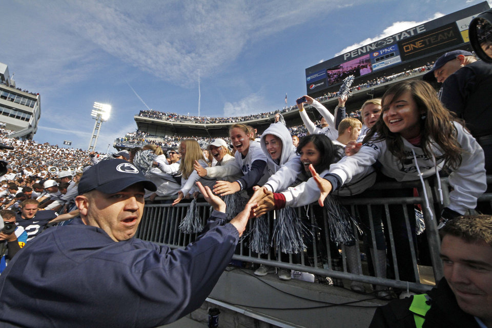 Penn State head coach Bill O\'Brien, left, celebrates with students as he leaves the field at Beaver Stadium following a 39-28 win over Northwestern in an NCAA college football game in State College, Pa., Saturday, Oct. 6, 2012. (AP Photo/Gene J. Puskar)