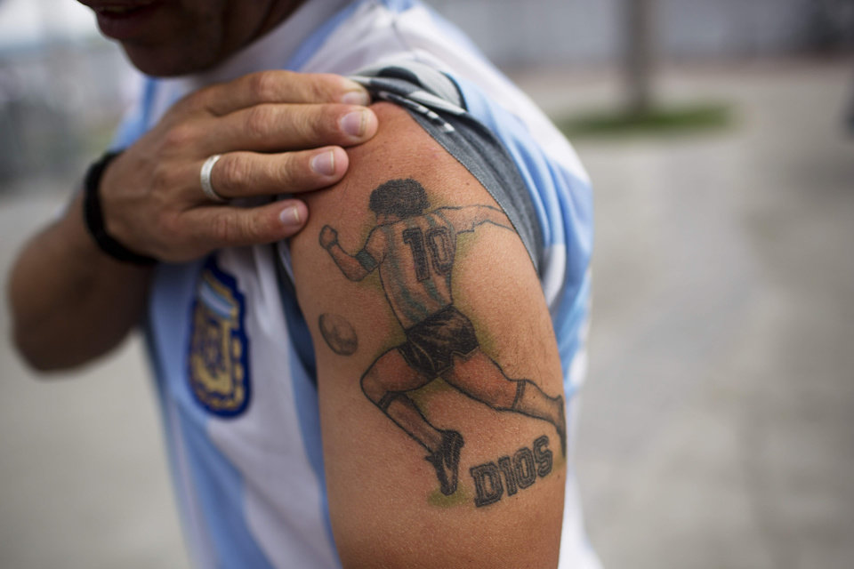 Photo - A soccer fan poses for a photo, raising the sleeve of his jersey to show off his his tattoo of Argentina's former soccer star Diego Maradona, outside the Maracana stadium in Rio de Janeiro, Brazil, Saturday, July 12, 2014. Argentina will face Germany in the World Cup final, Sunday. (AP Photo/Rodrigo Abd)