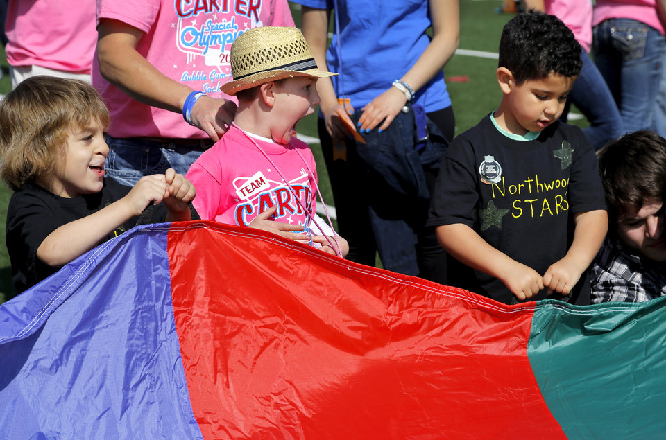 Photo - Carter Sudberry, 7, in the middle, joins children from Northwoods Fine Arts Academy in Sand Springs as they toss varying size balls onto a multi-hued piece of fabric and then tug on it to raise and lower the balls. These children are participating in activities on 'Stars of the Future' area south of Boone Pickens Stadium on the Oklahoma State University campus on Thursday, May 15, 2014. Special Olympics athletes numbering in the thousands are competing in various events today and tomorrow  in Stillwater as the organization's 45th Annual Summer Games are held in Oklahoma this week.  Officials say more than 4,600 Special Olympics Oklahoma athletes have registered to compete this year, and thousands of volunteers are assisting during the three days of competitions.   This is the 31st year the summer games has been centered at Oklahoma State University.  Special Olympics is the world's largest sports organization for children and adults with intellectual disabilities, providing year-round training and competitions to more than 4.2 million athletes in 170 countries, according to their web site. Photo by Jim Beckel, The Oklahoman