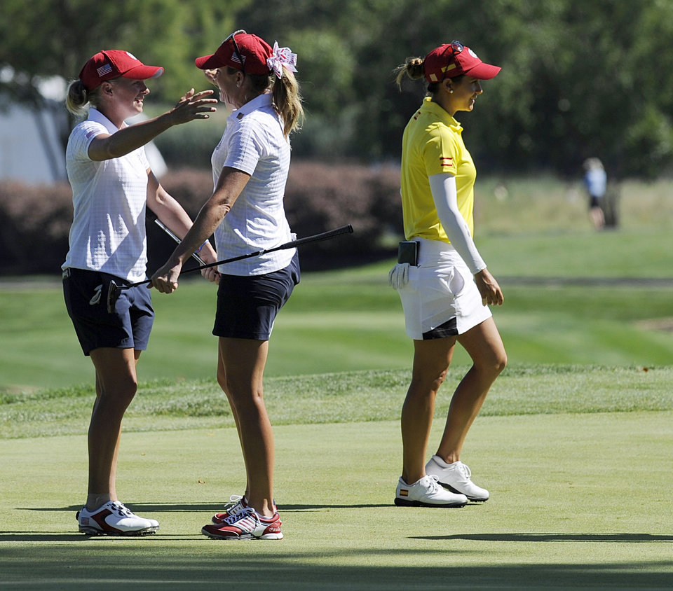 Photo - Stacy Wright, left, and Paula Creamer celebrate on the 18th hole as Azahara Munoz, right, of Spain, walks off the green during the second round of the International Crown golf tournament Friday, July 25, 2014, in Owings Mills, Md. (AP Photo/Gail Burton)