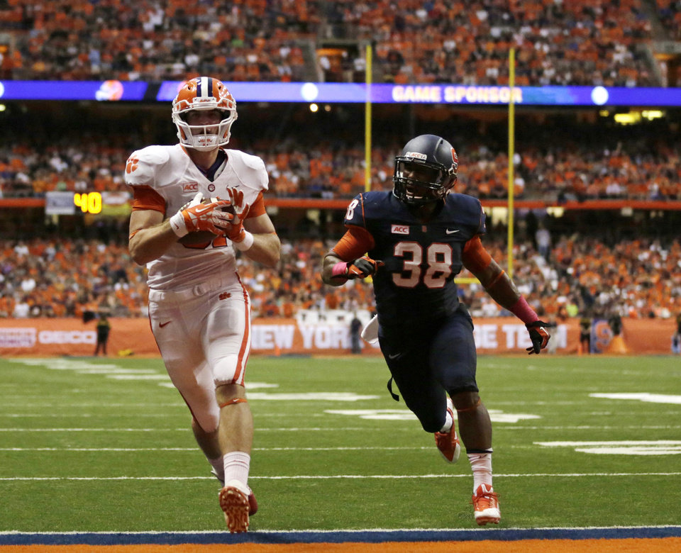 Photo - Clemson wide receiver Stanton Seckinger (81) scores a touchdown in front of Syracuse linebacker Cameron Lynch (38) during the first half of an NCAA college football game on Saturday, Oct. 5, 2013, in Syracuse, N.Y. (AP Photo/Mike Groll)