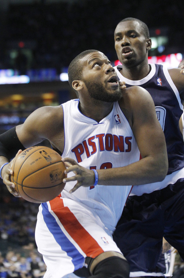Detroit Pistons center Greg Monroe (10) drives around Oklahoma City Thunder forward Serge Ibaka (9) during the first quarter of an NBA basketball game in Oklahoma City, Friday, Nov. 9, 2012. (AP Photo/Sue Ogrocki)
