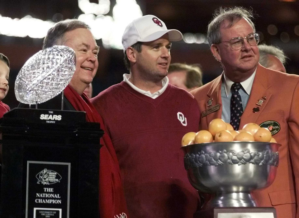 Photo - NATIONAL CHAMPIONSHIP, COLLEGE FOOTBALL: OU FLORIDA STATE ORANGE BOWL:  University of Oklahoma President David Boren, OU head coach Bob Stoops,  and Sherill Hudson, president of the Orange Bowl Committee pose with the BCS National championship trophy after the Sooners defeated the Florida State Seminoles in the Orange Bowl.  Staff Photo by Steve Sisney