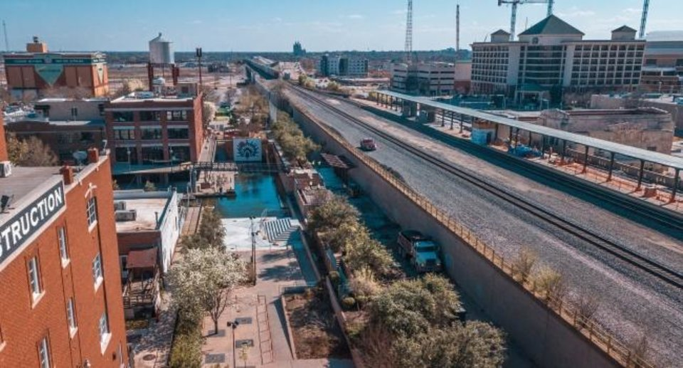 Photo -  When the Bricktown Canal first opened pedestrians had no access to the lower level from Sheridan or Reno Avenues and had to walk the long way next to the BNSF Railway viaduct to get from Sheridan Avenue to the southern side of the canal. A new stairway and bridge are shown in this aerial photo of the improved access. [Dave Morris/The Oklahoman]