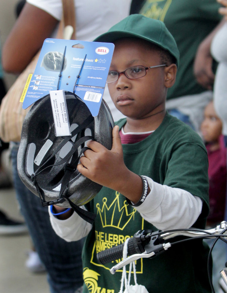 Photo -   ** ADDS MANDATORY CREDIT** Jamil Townsend, 8, a third grader at Crouse Elementary School, checks out the new bike helmet he received as part of the kick off event of the LeBron James Family Foundation's Wheels for Education