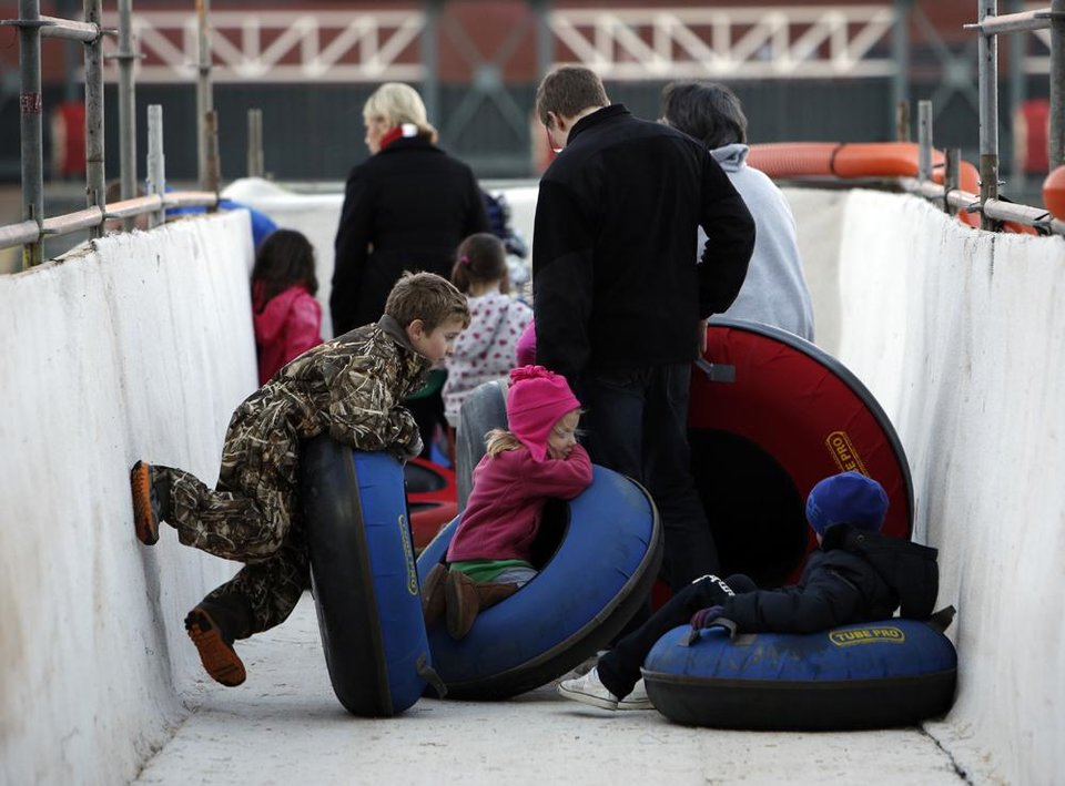 Photo -  People line up to ride tubes down a snow slope at Chickasaw Bricktown Ballpark in Oklahoma City, Saturday, Nov. 24, 2012.  Photo by Garett Fisbeck, The Oklahoman