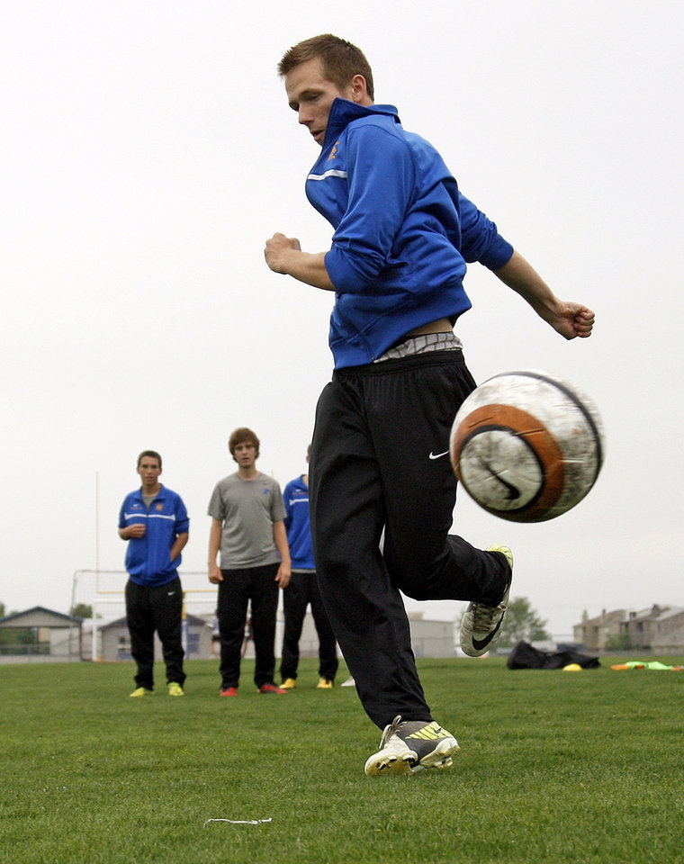 Photo - J.C. Bryan kicks the ball during soccer practice at Piedmont High School in Piedmont, Okla., Wednesday, April 11, 2012. Photo by Nate Billings, The Oklahoman