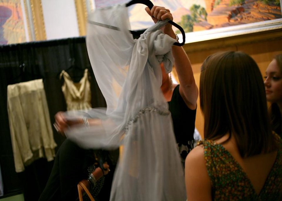 Photo -  A guest gets a close look at clothing desgned by and OSU student during a fashion show called Insight, a celebration of Culture and Style at National Cowboy and Western Heritage Museum in Oklahoma City on Tuesday, July 19, 2011. The show featured modern styles inspired by traditional Afghan and Rwandan attire. Students from Oklahoma State University designed and created some of the clothing featured in the show. All proceeds from the event benefit The Institute for Economic Empowerment of Women and their program called Peace Through Business. Photo by John Clanton, The Oklahoman
