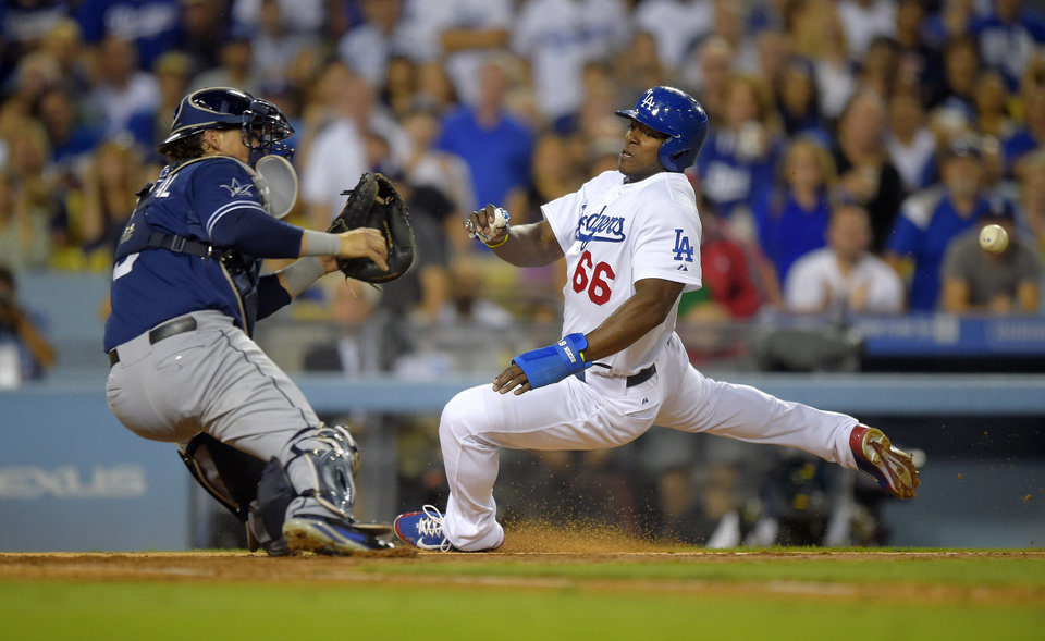 Photo - Los Angeles Dodgers' Yasiel Puig, right, scores on a sacrifice fly by Matt Kemp as San Diego Padres catcher Yasmani Grandal, tries to get to a throw that came in off line from center fielder Abraham Almonte during the third inning of a baseball game, Wednesday, Aug. 20, 2014, in Los Angeles. Almonte was charged with an error on the throw. (AP Photo/Mark J. Terrill)