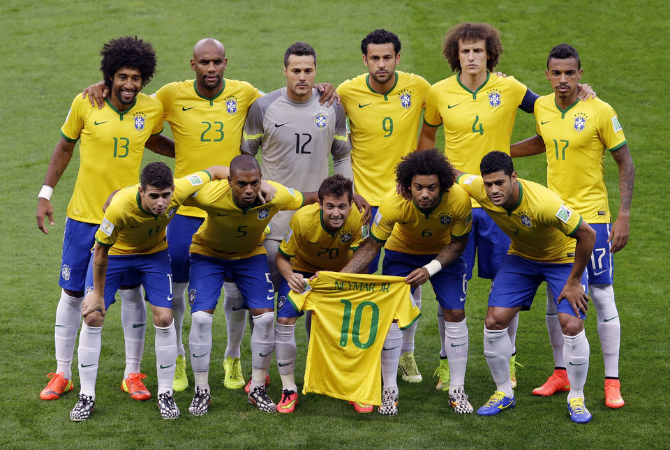 Photo - Brazil's Bernard, center, and Brazil's Marcelo hold the jersey of injured teammate Neymar as the team poses for photos before the World Cup semifinal soccer match between Brazil and Germany at the Mineirao Stadium in Belo Horizonte, Brazil, Tuesday, July 8, 2014. (AP Photo/Hassan Ammar)
