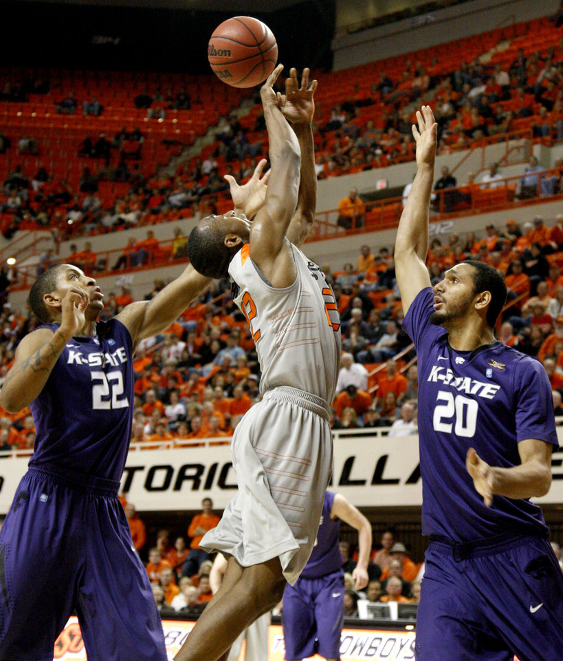 Photo - Oklahoma State's Markel Brown (22) goes for a rebound between Kansas State's Rodney McGruder (22) and Adrian Diaz (20) during an NCAA college basketball game between the Oklahoma State University Cowboys (OSU) and the Kansas State University Wildcats (KSU) at Gallagher-Iba Arena in Stillwater, Okla., Saturday, Jan. 21, 2012. Photo by Bryan Terry, The Oklahoman