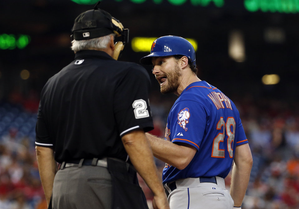 Photo - New York Mets' Daniel Murphy talks with home plate umpire Larry Vanover after striking out during the fourth inning of a baseball game against the Washington Nationals at Nationals Park Wednesday, Aug. 6, 2014, in Washington. (AP Photo/Alex Brandon)