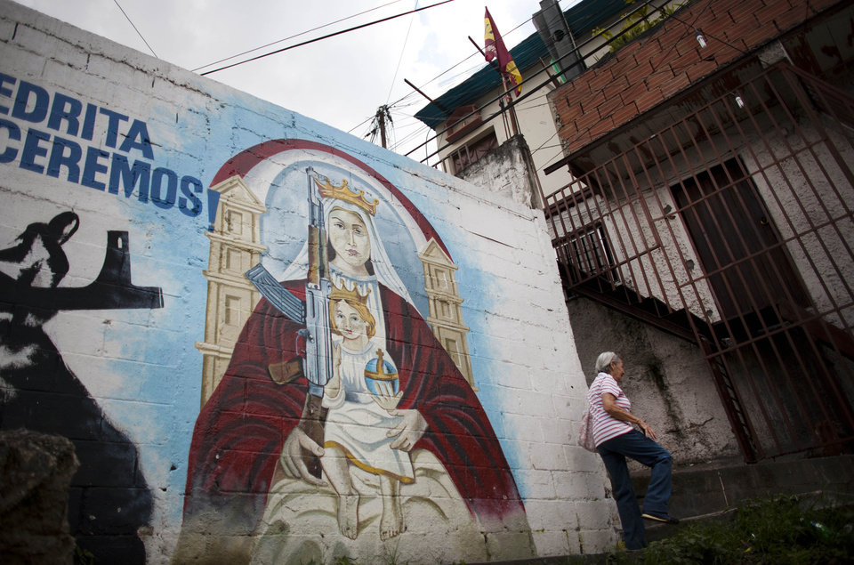 Photo -   In this Sept. 16, 2010, a mural depicts an image of the Virgin Mary holding Jesus and a machine gun a wall in La Piedrita or Little Rock neighborhood gang turf in Caracas, Venezuela. Heavily armed gangs that pledge allegiance to President Hugo Chavez rule over fiefdoms in slums where police rarely patrol, employing vigilante justice and collecting extortion money. A shooting attack on the opposition candidate's entourage has kindled worries that Chavez's defenders could resort to violence if cancer impedes his bid for re-election. The gangs, however, are loosely organized and do not appear to be taking orders from the government. (AP Photo/Ariana Cubillos)