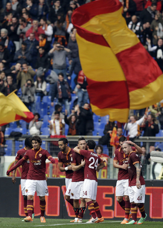Photo - AS Roma forward Francesco Totti, center, celebrates with his teammates after he scored during a Serie A soccer match between AS Roma and Genoa, at Rome's Olympic Stadium, Sunday, Jan. 12, 2014. (AP Photo/Andrew Medichini)