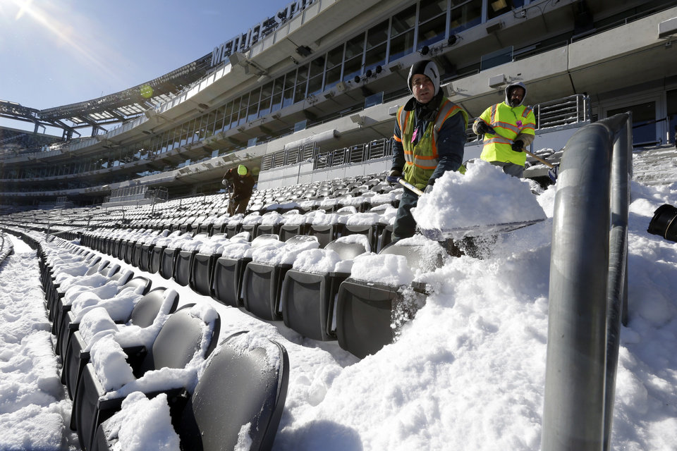 Photo - Workers shovel snow off the seating area at MetLife Stadium as crews removed snow ahead of Super Bowl XLVIII following a snow storm, Wednesday, Jan. 22, 2014, in East Rutherford, N.J. Super Bowl XLVIII, which will be played between the Denver Broncos and the Seattle Seahawks on Feb. 2, will be the first NFL title game held outdoors in a city where it snows. (AP Photo/Julio Cortez)