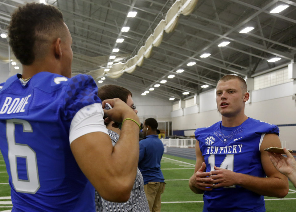 Photo - Kentucky's Patrick Towles, right, is interviewed as teammate Blake Bone (6) tries to distract him during the team's NCAA college football media day, Friday, Aug. 8, 2014, in Lexington, Ky. (AP Photo/James Crisp)