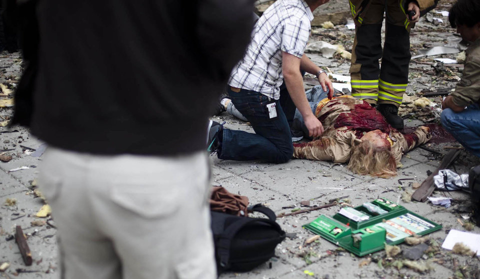 A victim is treated outside government buildings in the centre of Oslo, Friday July 22, 2011, following an explosion that tore open several buildings including the prime minister's office, shattering wiondows and covering the street with documents.(AP Photo/Fartein Rudjord)