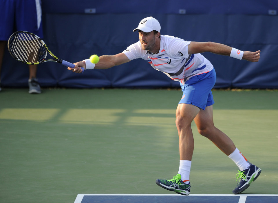 Photo - Steve Johnson lunges for the ball against John Isner against during a match at the Citi Open tennis tournament, Wednesday, July 30, 2014, in Washington. (AP Photo/Nick Wass)