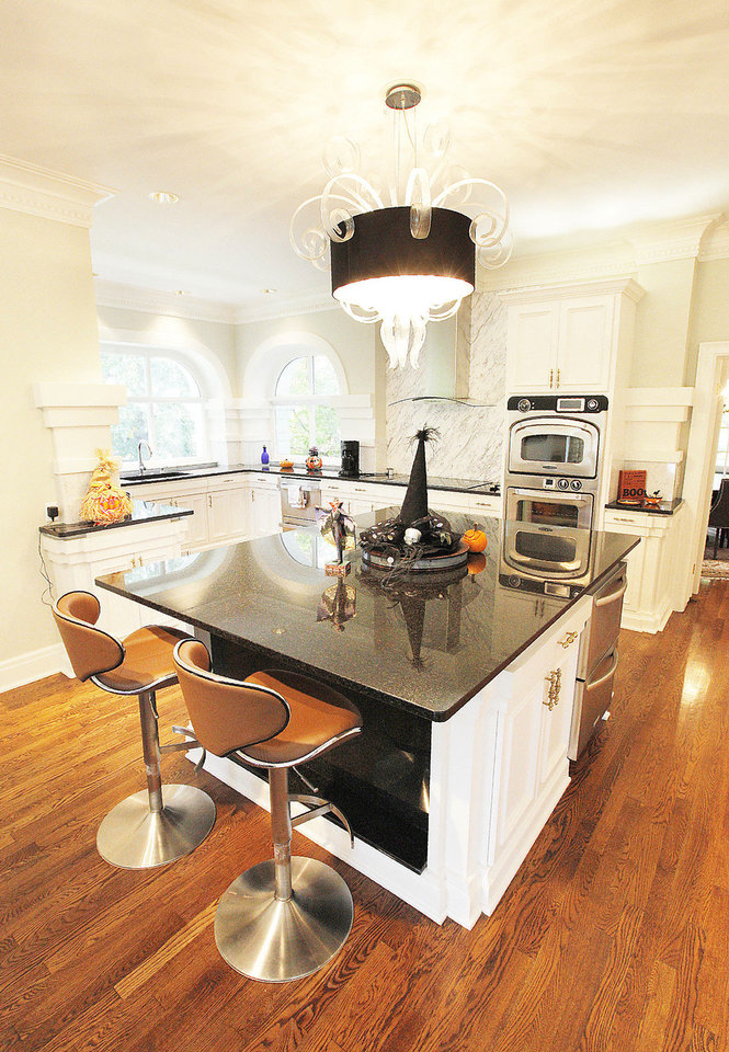 Photo - Dr. Diana Hampton's kitchen at 1715 N Hudson features a large island accented by a Murano glass jellyfish pendant light fixture.  PAUL B. SOUTHERLAND - The Oklahoman