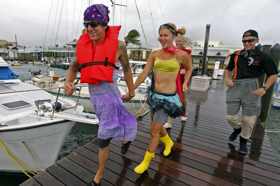 Anton Snitgen, Jenna Curl, Jackie Curl and Michael Manemut run along a dock at Key West Bight Marina in Key West, Fla., as Tropical Storm Isaac hits the area on Sunday, Aug., 26, 2012. Isaac gained fresh muscle Sunday as it bore down on the Florida Keys, with forecasters warning it could grow into a dangerous Category 2 hurricane as it nears the northern Gulf Coast. (AP Photo/The Miami Herald, Walter Michot)  ORG XMIT: FLMIH102