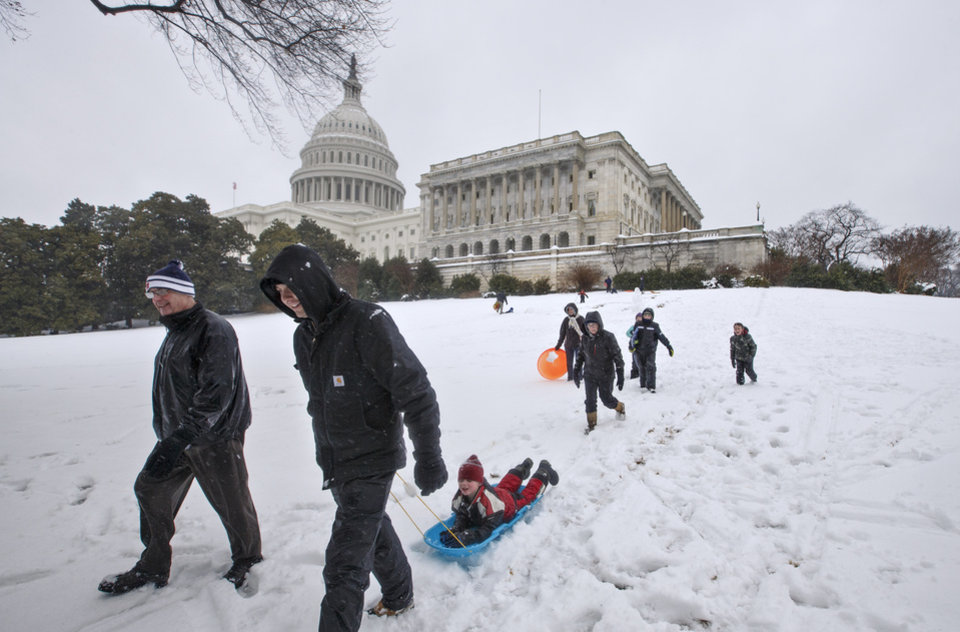 Photo - A family heads for home after a morning of fun in the snow on Capitol Hill in Washington, Thursday, Feb. 13, 2014, as winter weather shut down Washington. After pummeling wide swaths of the South, a winter storm dumped nearly a foot of snow in Washington as it marched Northeast and threatened more power outages, traffic headaches and widespread closures for millions of residents. (AP Photo/J. Scott Applewhite)