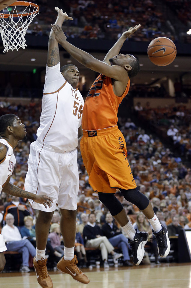 Oklahoma State\'s Markel Brown (22) is blocked by Texas\' Cameron Ridley (55) during the second half of an NCAA college basketball game, Saturday, Feb. 9, 2013, in Austin, Texas. Oklahoma State won 72-59. (AP Photo/Eric Gay) ORG XMIT: TXEG109