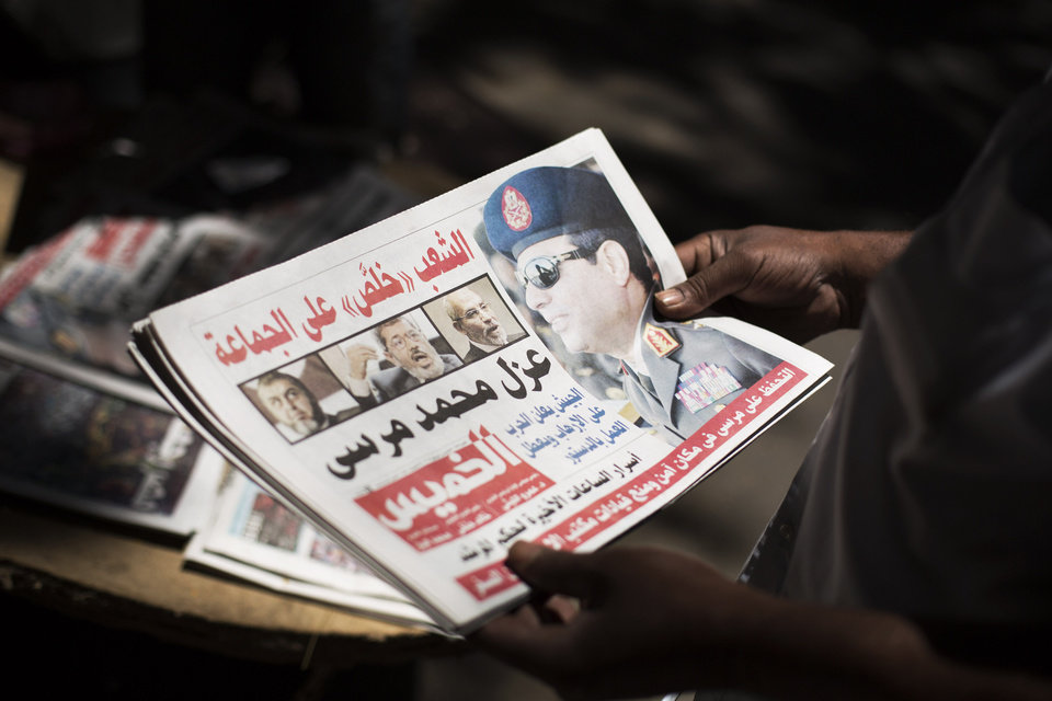 Egyptian man holds a newspaper the news near Mesaha Square, in Cairo , Thursday, July 4, 2013. The chief justice of Egypt's Supreme Constitutional Court was sworn in Thursday as the nation's interim president, taking over hours after the military ousted the Islamist President Mohammed Morsi. Adly Mansour took the oath of office at the Nile-side Constitutional Court in a ceremony broadcast live on state television. According to military decree, Mansour will serve as Egypt's interim leader until a new president is elected. A date for that vote has yet to be set.(AP Photo/ Manu Brabo)