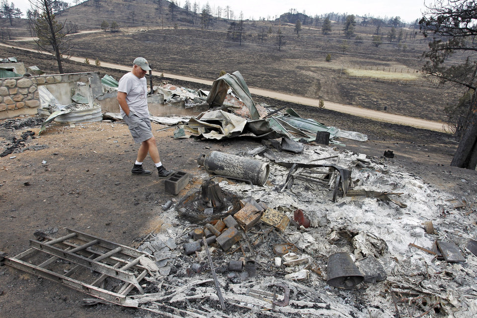 Photo - Martin Jiles looks over the ashes of his home that was destroyed by the High Park Fire in the Glacier View residential area near Livermore, Colo., on Monday, July 2, 2012. The last evacuees from the fire in have been allowed to return home as crews fully contained the136-square-mile wildfire that killed one resident and destroyed 259 houses. (AP Photo/Ed Andrieski) ORG XMIT: COEA101