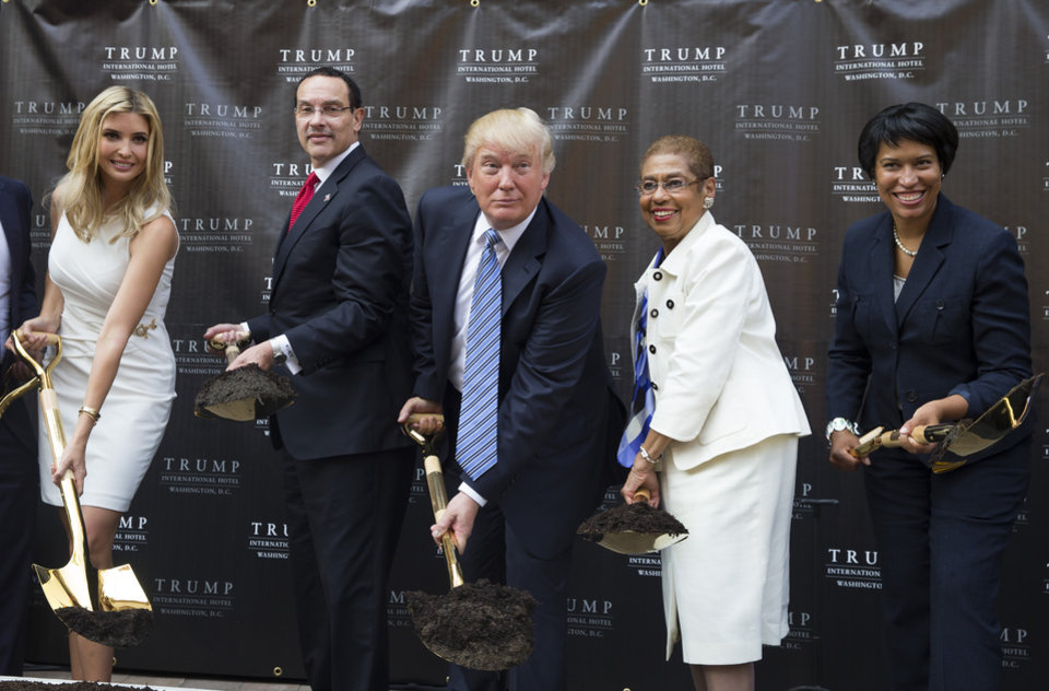 Photo - Donald Trump, center, poses for photographs during a ground breaking ceremony for the Trump International Hotel on the site of the Old Post Office, on Wednesday, July 23, 2014, in Washington. From left, Ivanka Trump, Washington Mayor Vincent Gray, Trump, Del. Eleanor Holmes Norton, D-D.C., and Muriel Bowser, the Democratic nominee for D.C. mayor. (AP Photo)