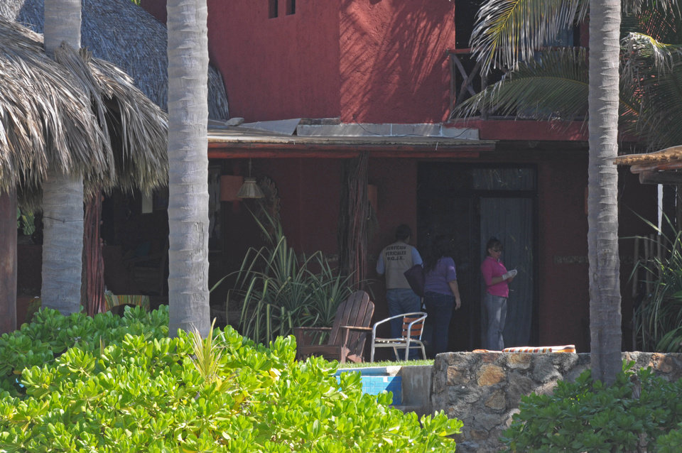 Photo - Police investigators work at a home after masked, armed men broke into the home in Acapulco, Mexico, Tuesday Feb. 5, 2013. According to the mayor of Acapulco, five masked men burst into this house that Spanish tourists had rented on the outskirts of Acapulco, in a low-key area near the beach, and held a group of six Spanish men and one Mexican woman at gunpoint, while they raped the six Spanish women before dawn on Monday. (AP Photo/Bernandino Hernandez)