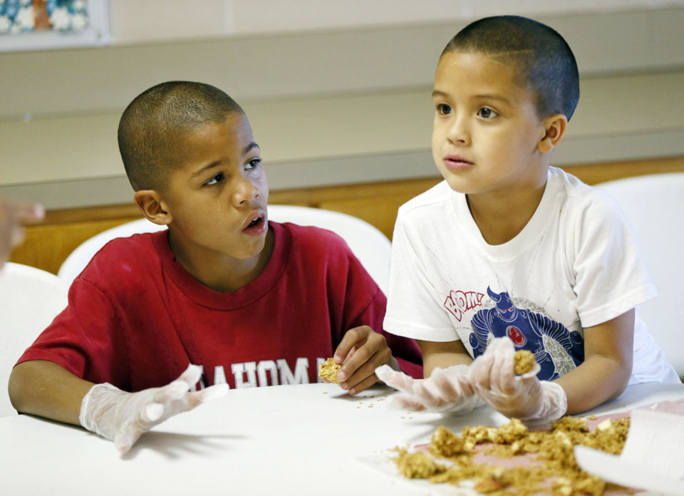 Photo - Maleek Jackson, 8, left, and Aroon Lopez, 5, talk as they eat Peanut Butter Apple Oat Snacks they helped to make during a cooking demonstration as part of Food Day activities at the Salvation Army Boys and Girls Club, 2808 SE 44th St., one of the Regional Food Bank of Oklahoma's Kids Cafe locations, in Oklahoma City, Thursday, Oct. 24, 2013. Photo by Nate Billings, The Oklahoman