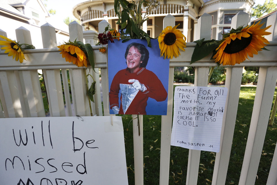 Photo - A photo of the late actor Robin Williams playing Mork from Ork hangs with flowers and notes left by people paying their respects, at a makeshift  memorial in Boulder, Colo., Tuesday Aug. 12, 2014, outside the home where the 80s TV series Mork & Mindy, starring Williams, was set. Williams, the Academy Award winner and comic supernova whose explosions of pop culture riffs and impressions dazzled audiences for decades and made him a gleamy-eyed laureate for the Information Age, died Monday, Aug. 11, in an apparent suicide. He was 63. (AP Photo/Brennan Linsley)