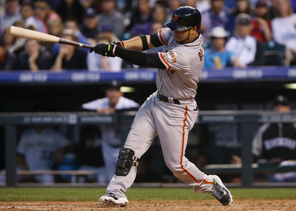 Photo - San Francisco Giants' Gregor Blanco follows through with his swing after connecting for a triple to drive in two runs against the Colorado Rockies in the fifth inning of a baseball game in Denver on Tuesday, May 20, 2014. (AP Photo/David Zalubowski)