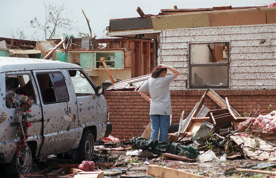 MAY 3, 1999 TORNADO: Tornado victims, damage: Midwest City. Kim Paz, of 6108 SE 7, surveys the damage to her house. She did not make it into the closet and was trapped and received glass in her back and wood splinters in her foot.