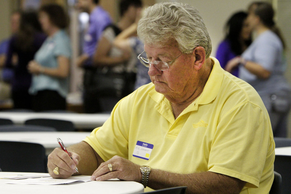 Mike Simmons, of Oklahoma City, fills out a questionnaire Thursday during the Tornado Town Hall meeting at the Norman Public Library. Photo by David McDaniel, The Oklahoman   <strong>David McDaniel</strong>