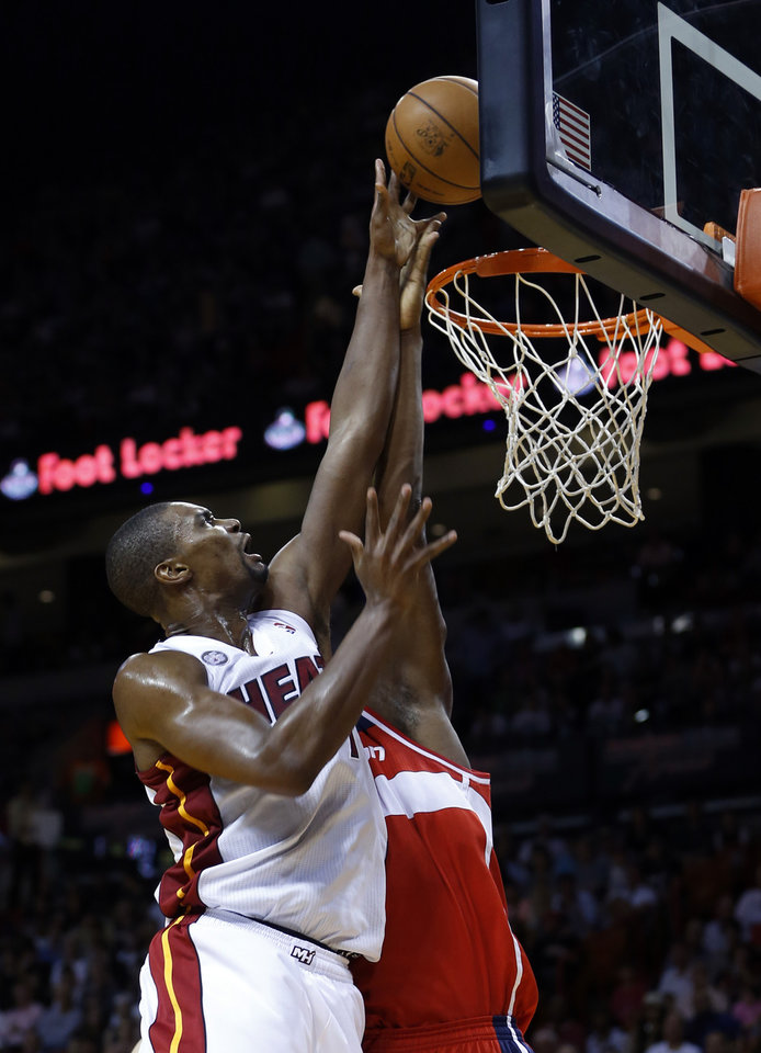 Miami Heat's Chris Bosh (1) goes to the basket against Washington Wizards' Bradley Beal (3) during the first half of an NBA basketball game in Miami, Sunday, Jan. 6,  2013. (AP Photo/Alan Diaz)