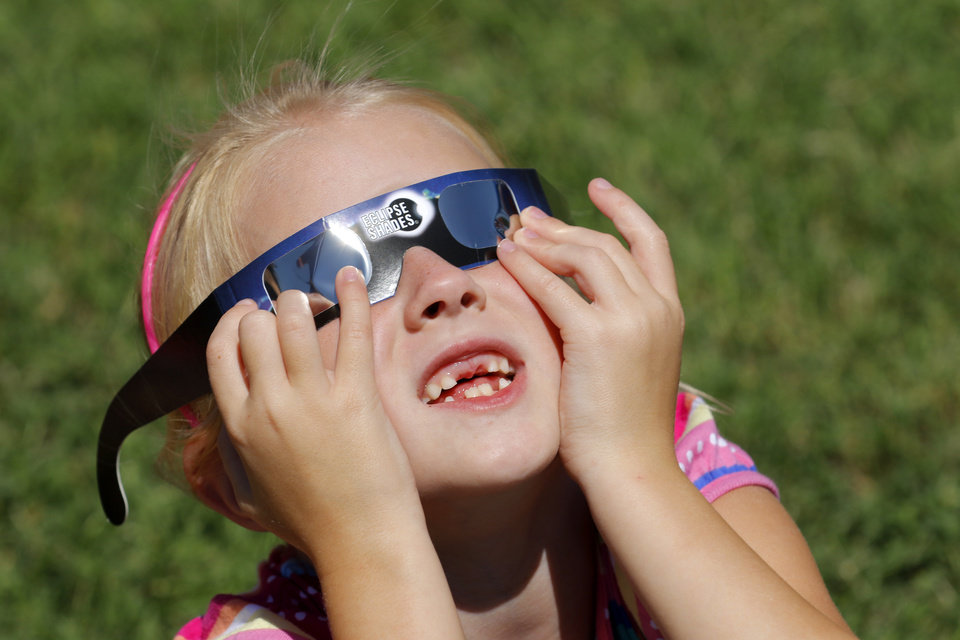Photo - Emerson Edwards 2nd grade watches the eclipse at Washington Irving Elementary School in Edmond, Monday August 21, 2017. Emerson joined other students, parents and teachers in viewing the eclipse. Photo By Steve Gooch, The Oklahoman