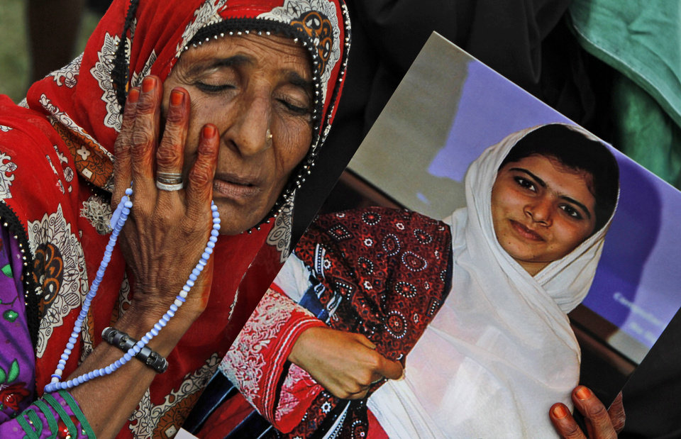 Photo -   A supporter of Pakistani political party Muttahida Qaumi Movement (MQM), reacts while holding a poster of 14-year-old schoolgirl Malala Yousufzai, who was shot last Tuesday by the Taliban for speaking out in support of education for women, during a rally to condemn the attack in Karachi, Pakistan, Sunday, Oct. 14, 2012. Tens of thousands rallied in Pakistan's largest city Sunday in support of a 14-year-old girl who was shot and critically wounded by the Taliban for promoting girls' education and criticizing the militant group. (AP Photo/Shakil Adil)