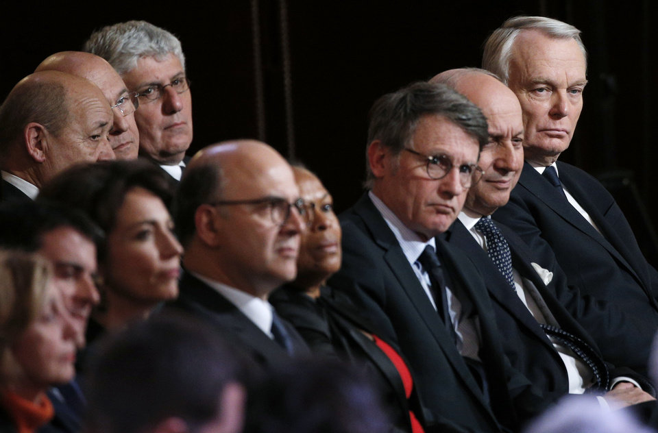 Photo - Members of the government, with Prime Minister Jean-Marc Ayrault, right, listen to French President Francois Hollande delivering his speech at his annual news conference, Tuesday, Jan.14, 2014 at the Elysee Palace in Paris. Hollande is promising to cut 50 billion euros in public spending over 2015-2017 to try to improve the indebted economy. Hollande, a Socialist, came to office in 2012 on pledges to avoid the painful austerity measures carried out by neighboring Spain and Italy. But France's economy has suffered two recessions in recent years and growth is forecast at an anemic 0.2 percent in 2013. (AP Photo/Christophe Ena)