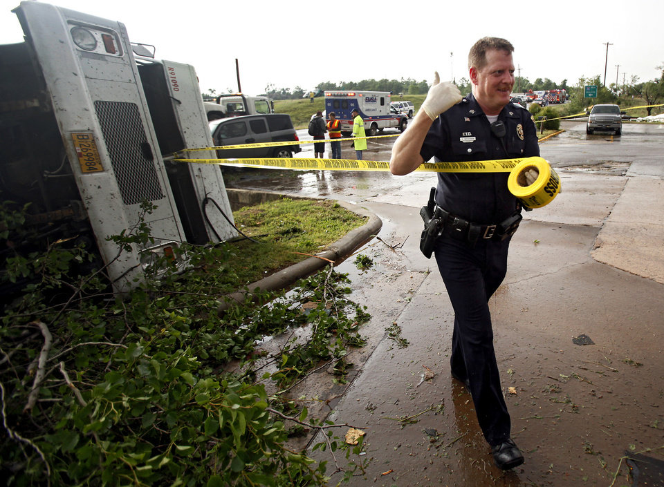 Photo - A police officer secures the area around the Loves Country Store with crime tape after a tornado damaged the area around I-40 and Choctaw Road on Monday, May 10, 2010, in Oklahoma City, Okla.  Photo by Chris Landsberger, The Oklahoman