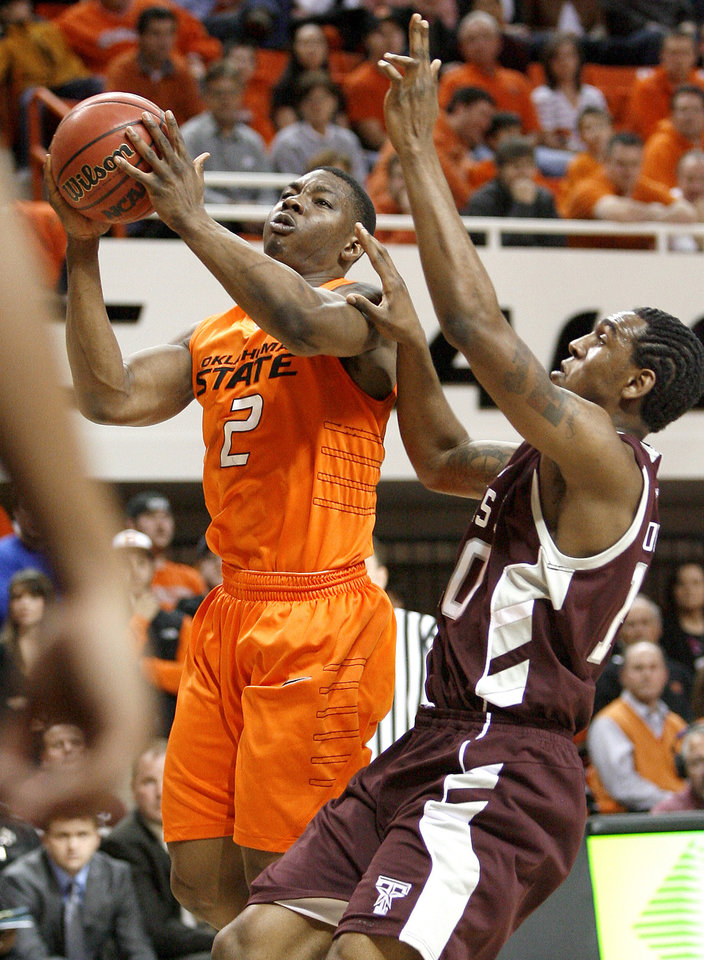 Photo - OSU's Obi Muonelo drives past Texas A&M's David Loubeau during an NCAA college basketball game between the Oklahoma State University and Texas A&M at Gallagher-Iba Arena in Stillwater, Okla., Wednesday, January 27, 2010. Photo by Bryan Terry, The Oklahoman