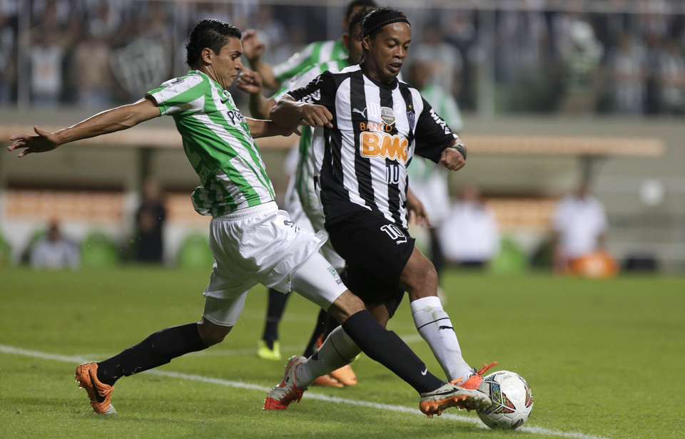 Photo - Daniel Bocanegra of Colombia's Atletico Nacional, left, fights for the ball with Ronaldinho of Brazil's Atletico Mineiro during a Copa Libertadores soccer match in Belo Horizonte, Brazil, Thursday, May 1, 2014. (AP Photo/Bruno Magalhaes)